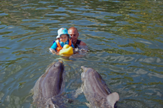 Emilia bei der Delphintherapie mit dem Trainer